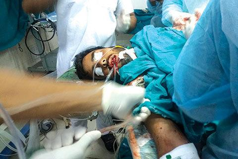 Doctors trying to save the life of a pellet and bullet hit victim in the operation theatre.