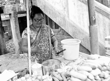 A lady selling fruits near Junction, Siliguri. She has been doing this for the last 7 years and is independently piloting her family. Siliguri, 2018